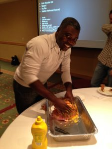 """A TeamSnap company meeting tradition is to give """"passion talks"""" in which you discuss something you enjoy outside of work. Here, Alondo Brewington gives a brisket a rub during BBQ Master Ryan Grablick's passion talk."""