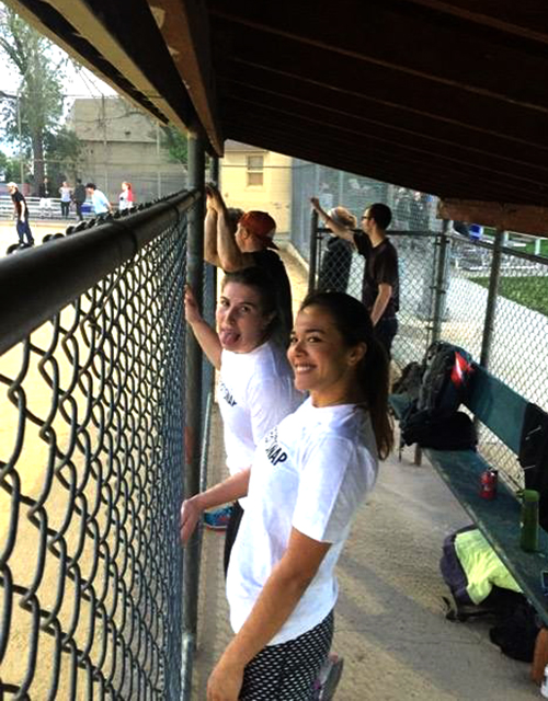 Sales Team Members Aliza and Ashley Frese ham it up in the dugout of one of TeamSnap's kickball games.