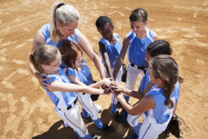 Softball players with coach in huddle doing team cheer