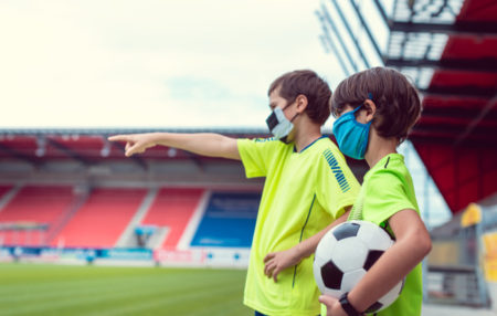 two youth soccer players pointing at the field and talking