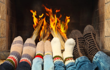 people warming their feet by a fire