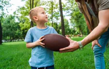 photo of a little boy holding a football