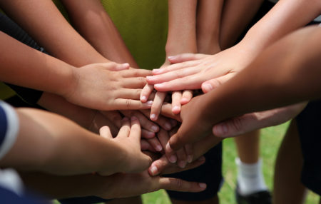 group of young people with their hands together in a circle