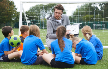 photo of a coach showing his youth soccer team a game plan