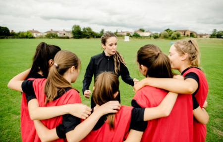 female sports team huddled together on a field