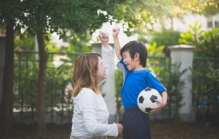 mom and son cheering while playing soccer